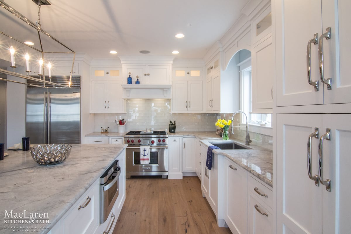 White Classic Countertops And Cabinetry Complimented With Rustic Flooring  For A Beachy Feel