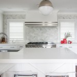Cambria Quartz Countertops in White Cliff complimented by a Backsplash of Herringbone Pattern in Polished Carrara Tile